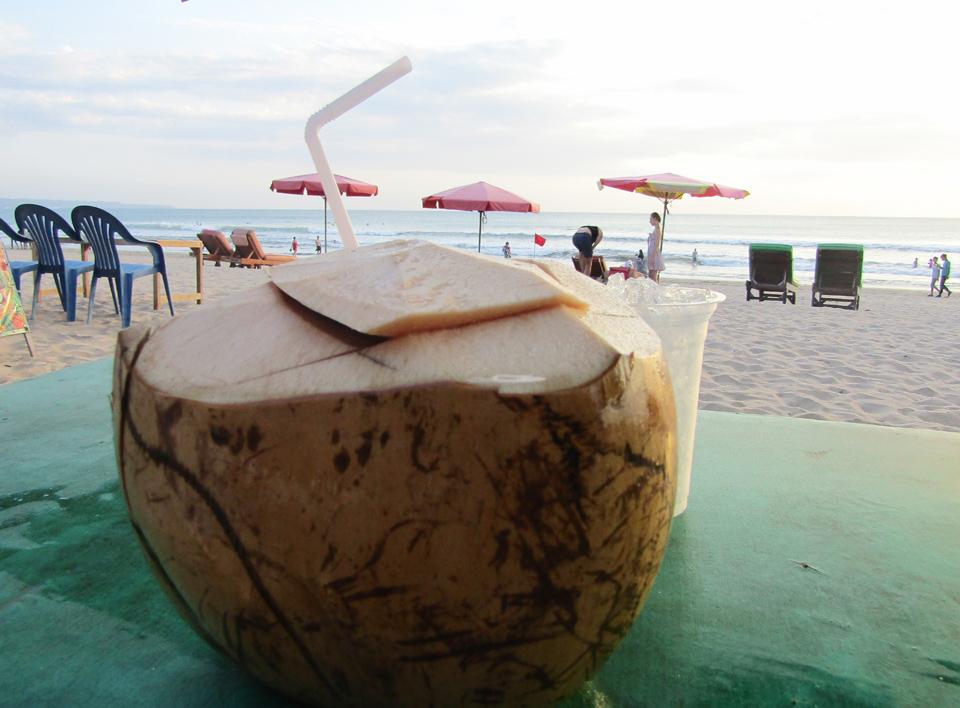 minum kelapa muda ala pantai kuta bali